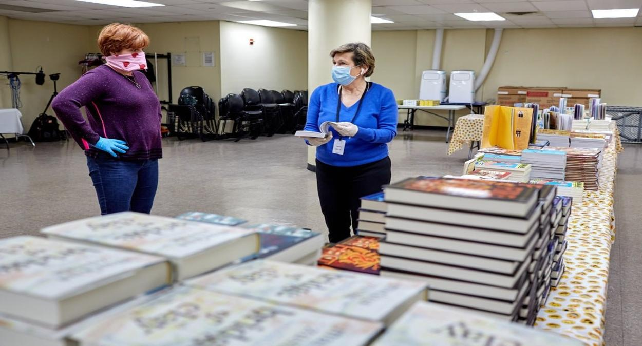 Two Mars Associates from AMERICAN HERITAGE® Chocolate wearing masks beside donated books.